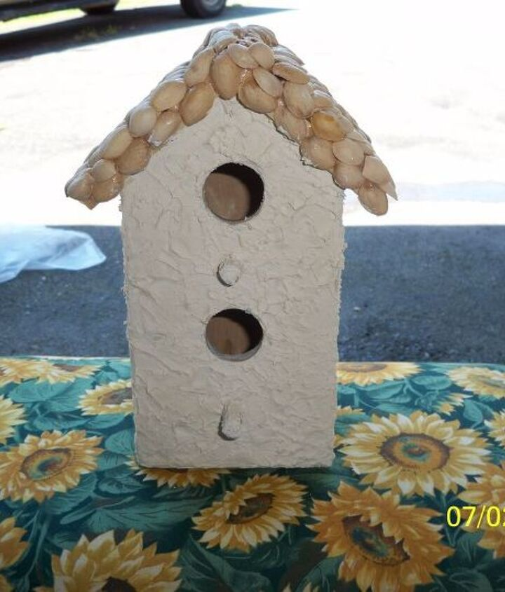 Simple wooden birdhouse w/pistaschio shells on the roof