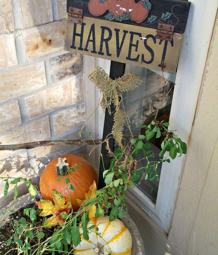 A couple of pumpkins and a harvest yard sign take the potted plant from Summer to Fall.