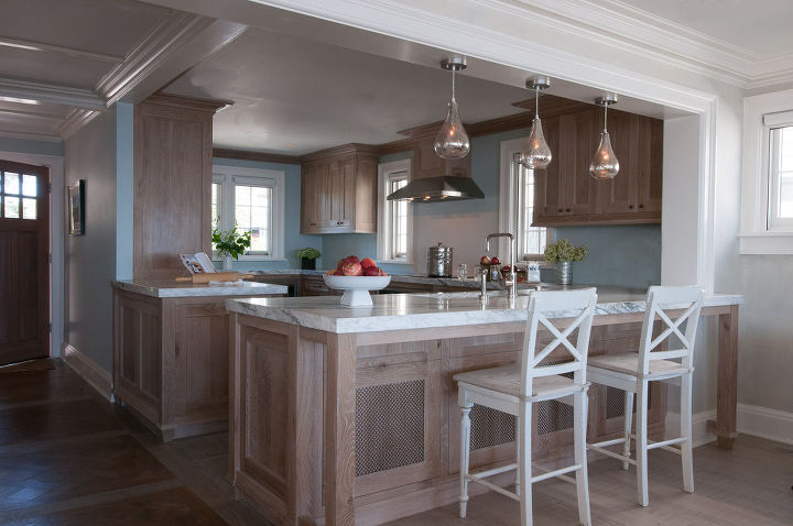 Every piece of cabinetry and wainscoting was custom built, lending the home a solid and memorable essence of enduring beauty. Kitchen cabinets were custom made in white oak with a limed wood finish by Titus Built, LLC.