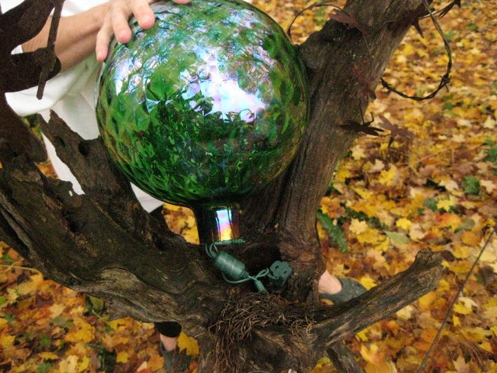 Placing the gazing ball onto the top of the log.