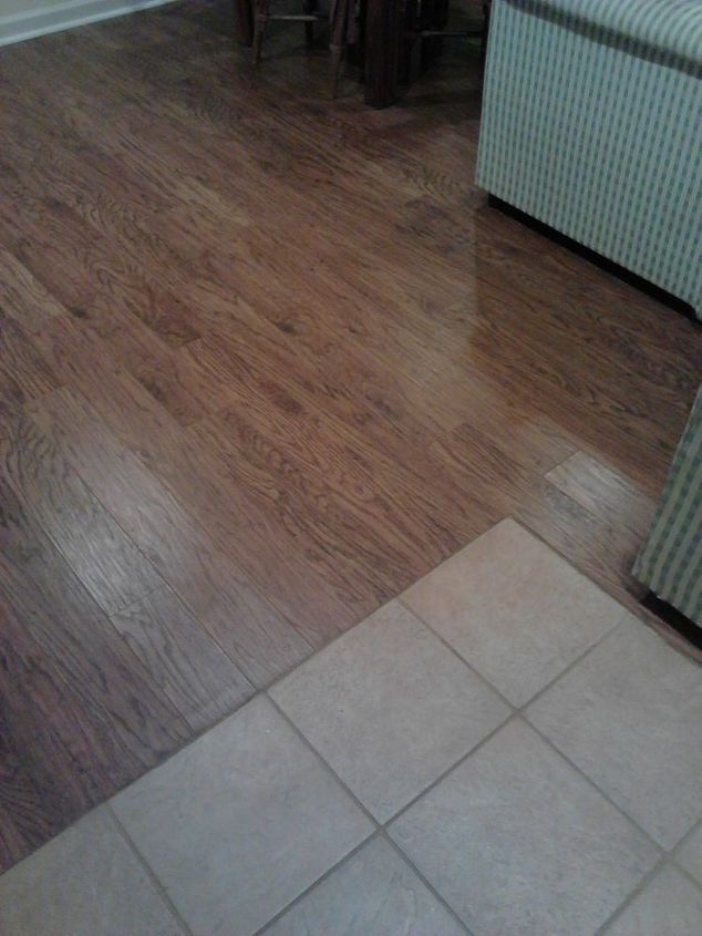 Silicone caulk to eliminate the toe kicker between the ceramic floor and the laminate....