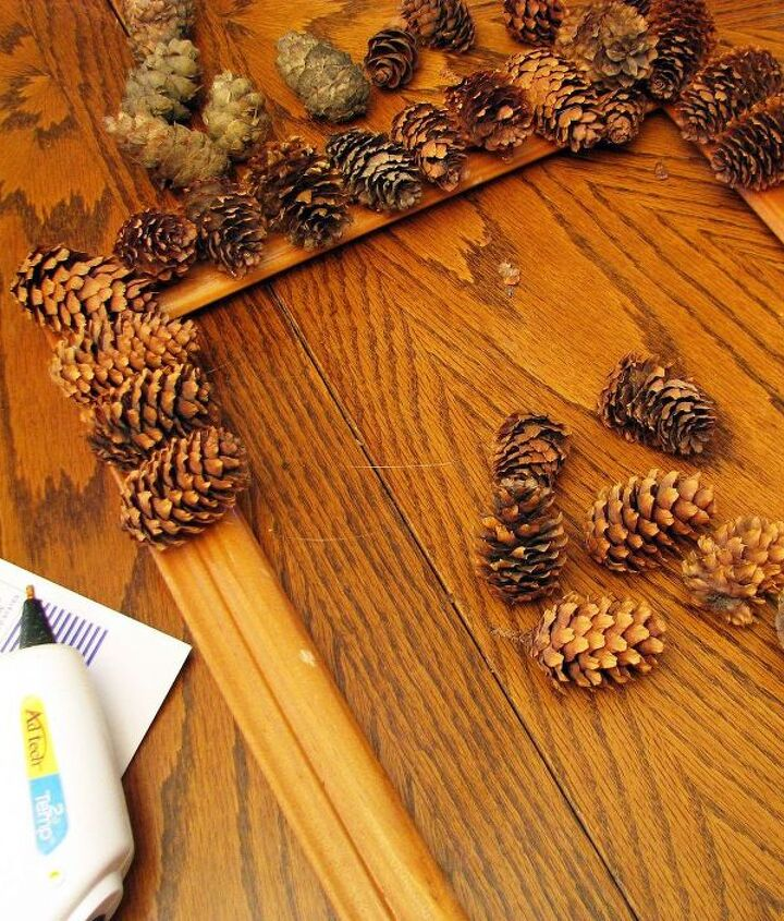 Glue gun, old wooden frame, a bit of ribbon and pine cones is all you need!