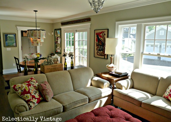 A small room is cozy with a l shaped furniture arrangement and a big ottoman for propping up your feet. http://eclecticallyvintage.com/2012/05/family-room-tour-breakfast-nook/