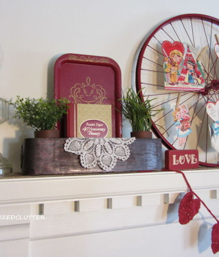 "Other items in the vignette, include oil lamps, a lantern, doilies, faux greenery, a head vase, a ""love"" sign, a heart garland, a sewing machine drawer, a red tray, a book,  and a felt red rose."