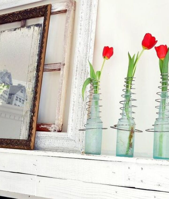 Vintage bed-springs on old bottles hold red tulips on the mantle.