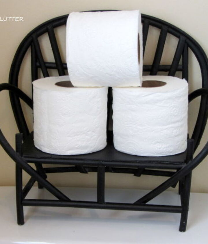 Toilet paper on a twig chair on the back of the toilet.