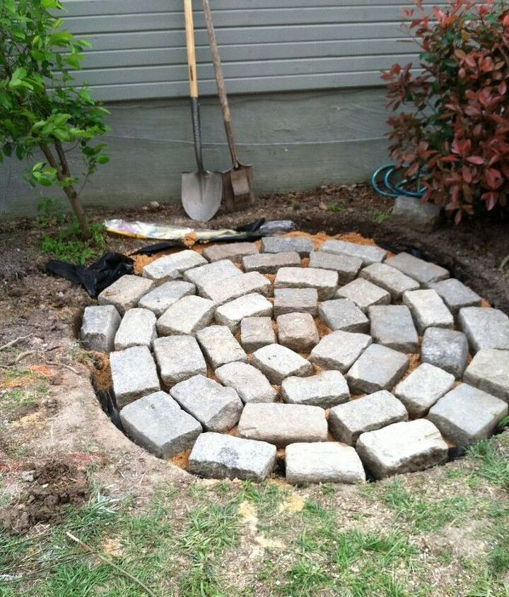 recycled granite block patio, outdoor living, patio, I dug my hole about 3 4 inches deeper than the stones I covered the base of the hole with a layer of weed block fabric then 2 3 inches of sand I laid out stones in a circular pattern starting in the center