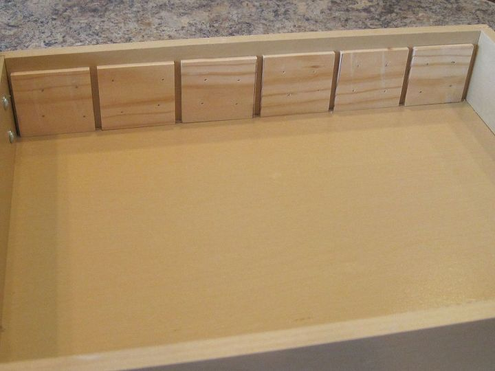 I wanted the unit to be removable, so, after figuring out the measurements, my husband took them & nailed these small spacers onto one side of the drawer.  Eventually, the slats would slide into them.