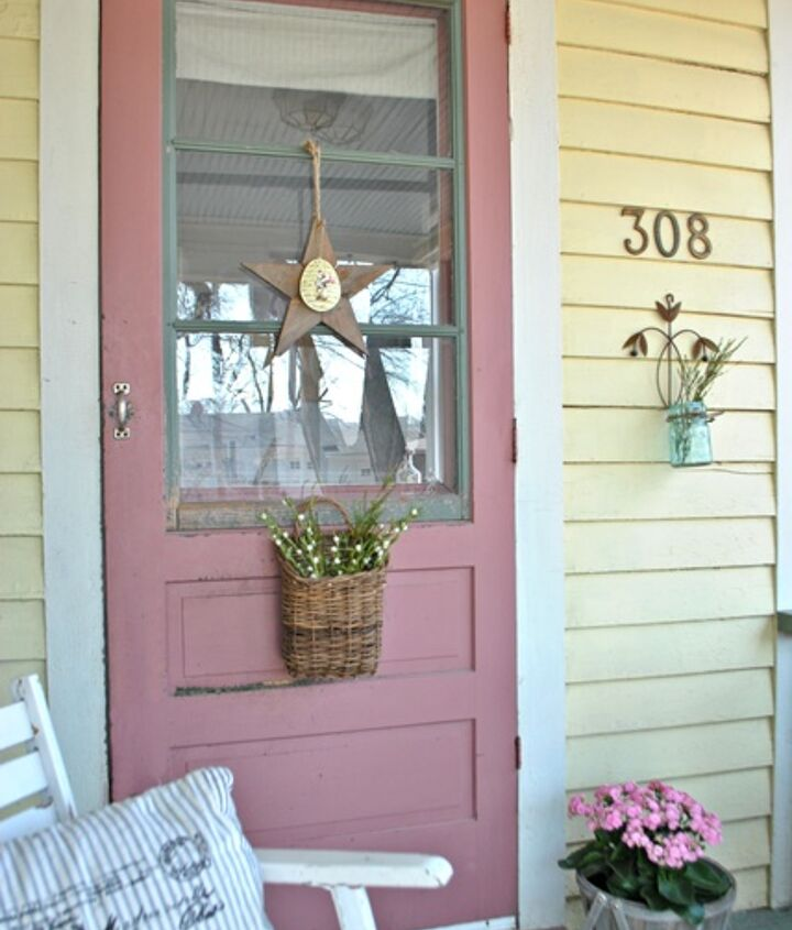 Simple decorations like a wooden star and rustic basket flank a farmhouse door.