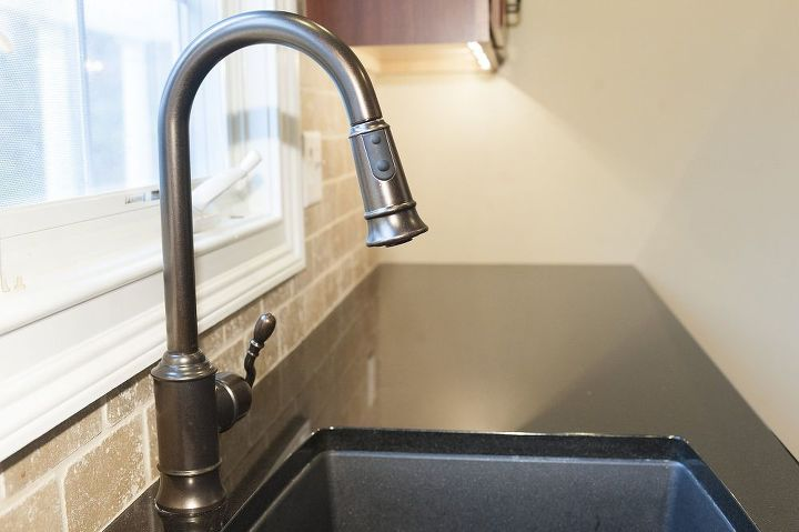 Black absolute granite counter with Moen Woodmerer single lever faucet.