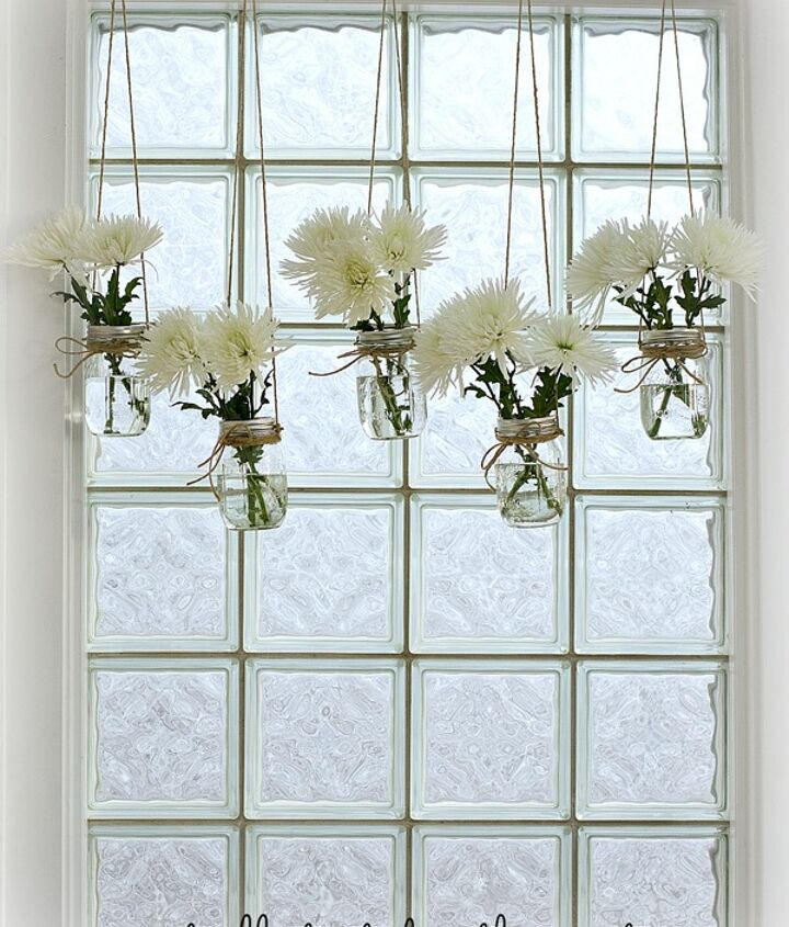 Mason jar window treatment using jute rope and fresh flowers.