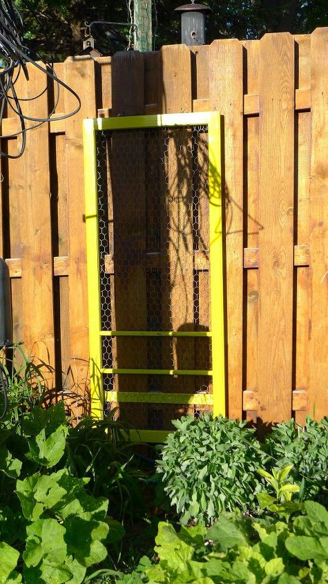 This is the insert from an old screen door. I painted it and inserted chicken wire (also from a garage sale). Brightening up the alley is fun!