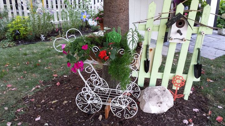 Little green fence and flower carriage adorn the tree.