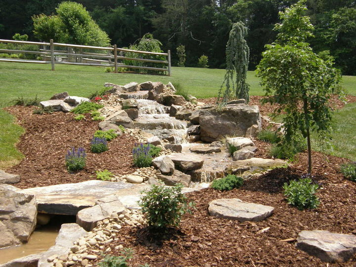 The pondless waterfall is accentuated by colorful perennials and unique specimen plantings.