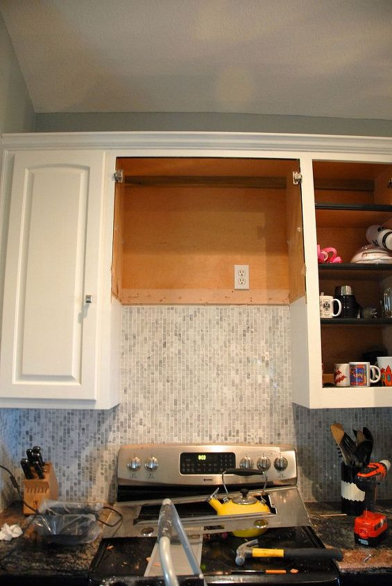The demoed out cabinet. Let me add since I had a comment about the mess on the stove - the stove is broken. My husband cracked it and I only have one functioning burner. When you do this remove the stove (or at least cover it).