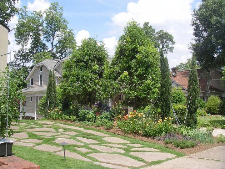 AFTER photo. See pruned and limbed up holly trees, Italian cypress set in groups of 3 to either side, summer perennials and herbs in this Atlanta area front yard in Virginia Highlands