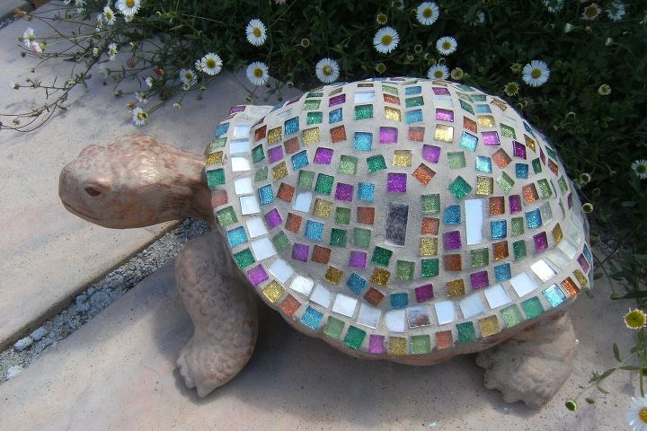 A closer inspection of Joseph's 'coat'.   He was made using a store-purchased ceramic mold, to which I added small mosaics in jewel tones, with some mirror tiles.  The head and feet were painted with bronze craft paint.