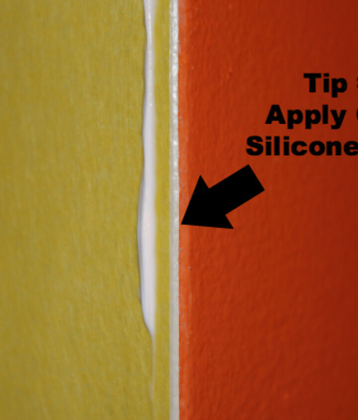 Then apply clear silicone caulk between the Frog Tape and wall. This caulk will dry clear but goes on white.