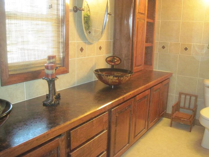 Stained cherry cabinets, laminate counter and vessel sinks.