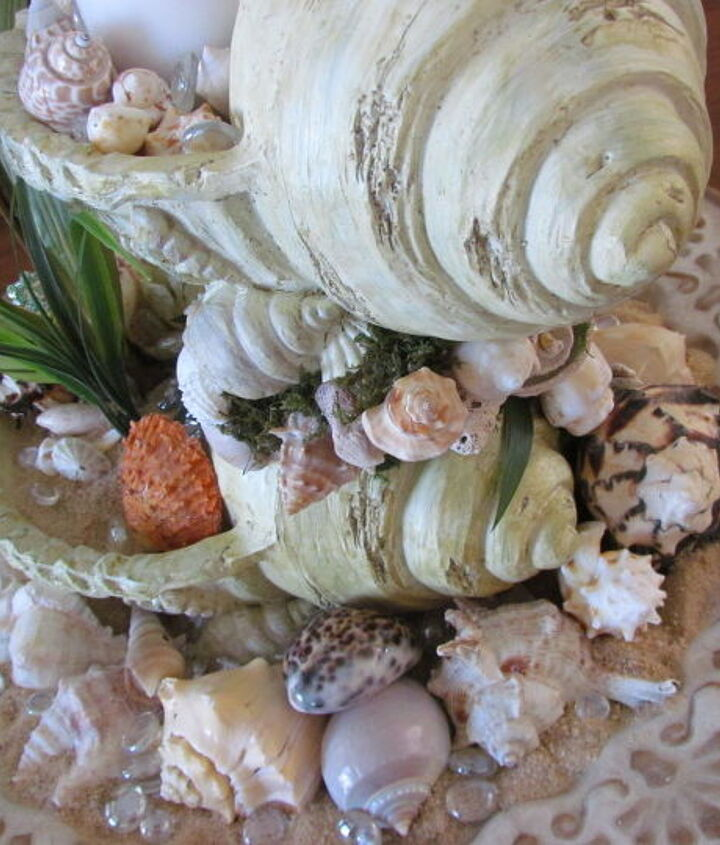 I sat it in a round tray that has a inner scallop design, filled the tray with sand, shells and clear glass rocks