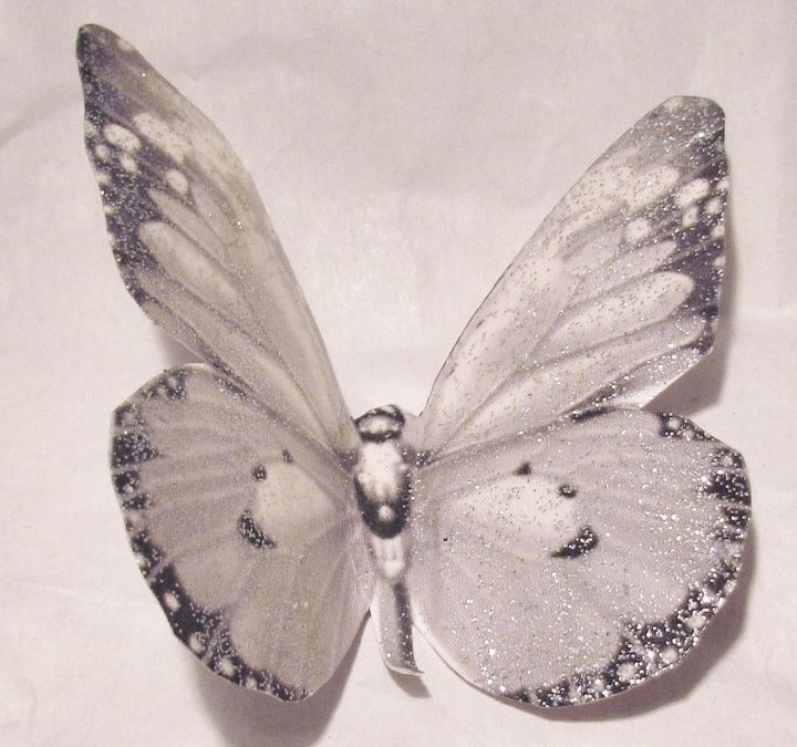 Printed butterflies from clipart in the color I wanted. Made two copies. Mod Podge the two copies together back to back. So the butterflies had thickness. Brushed one side with glitter. Cut and folded the wings up.