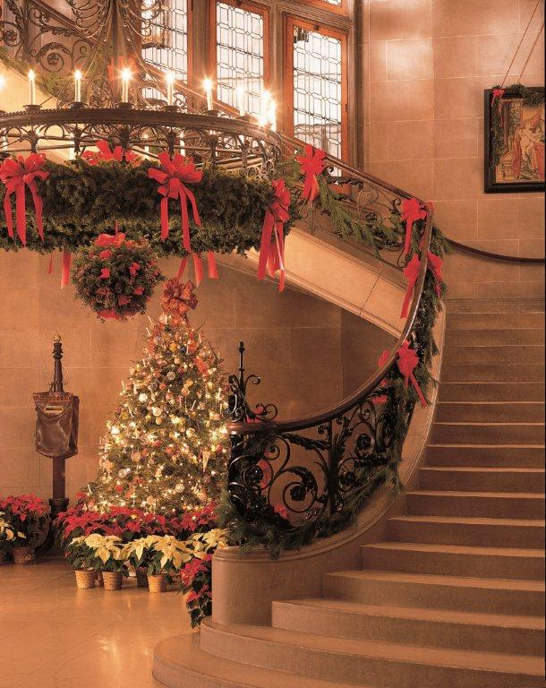 The Grand Staircase is twined with evergreens, filling the 250 rooms with the scent of