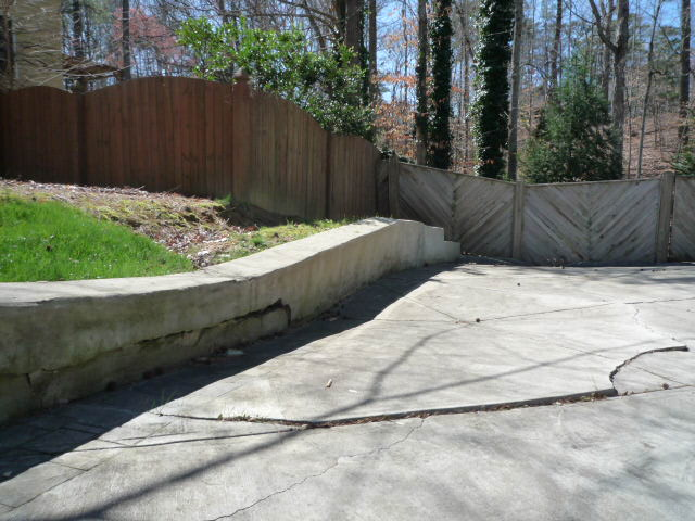 Ground behing fence at end of driveway slopes down maybe 10 ' to the backyard