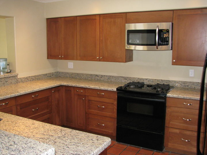 Our goal was to minimize the cost of this kitchen remodel while creating maximum value to our clients. We replaced a minimum number of the cabinets for practical reasons such as relocating the microwave to its new location over the stove.