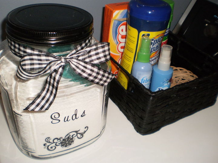 I purchased this plain jar at Wal Mart, spray painted the lid black, embellished it with some scrapbook stickers, and tied a black and white gingham bow on it to spruce it up a bit. A nicer alternative to those ugly wash powder boxes.
