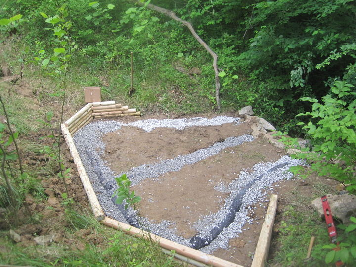 creating a creek stone patio amp fire pit, concrete masonry, outdoor living, patio, Then he dug a trench installed the french drain basically a pipe with holes in the top that collects water channels it where you want it to go covered it with gravel Then he added a timber retaining wall