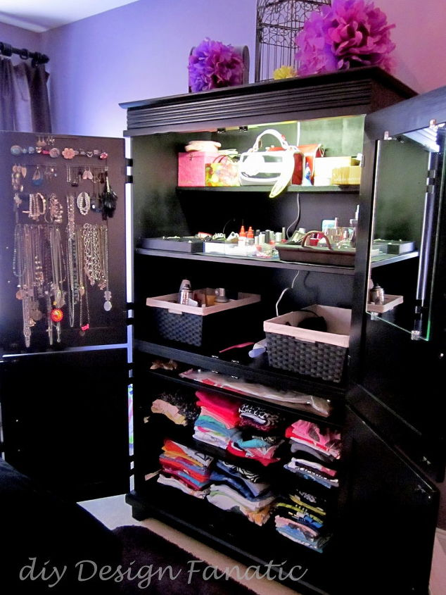 The left top door of the armoire holds jewelry, a mirror is mounted on the right top door. The baskets hold hair products and tools and folded tshirts are on roll out shelves in the lower part of the armoire.