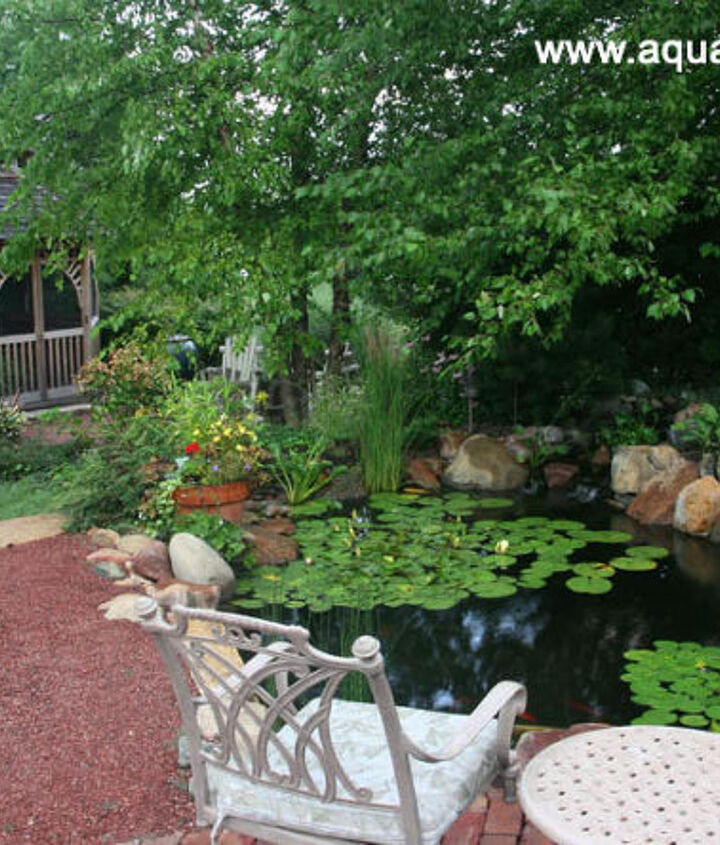 A bridge across the water garden leads to a gazebo, waterfall, and firepit.