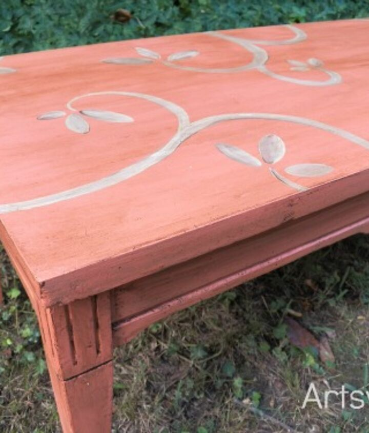 Coral coffee table painted with homemade chalk paint, a design added with acrylic paint, and then finished off with a coat of dark wax.