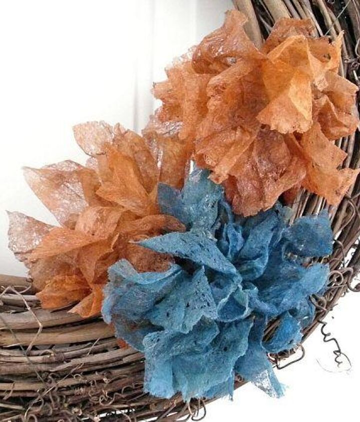 """I added my dryer sheet flowers to a plain grapevine wreath that hangs on the inside of our front door. Our accent color in our home is teal, so this is a perfect """"merge"""" of Fall colors!"""