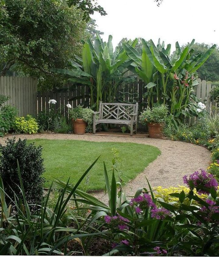 A circular walk and bench set off a small throw-rug lawn and mixed flowers and shrubs.