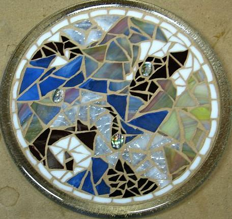 A variety of colors and patterns of glass, plus small mother of pearl cabochons make up this kitchen trivet.