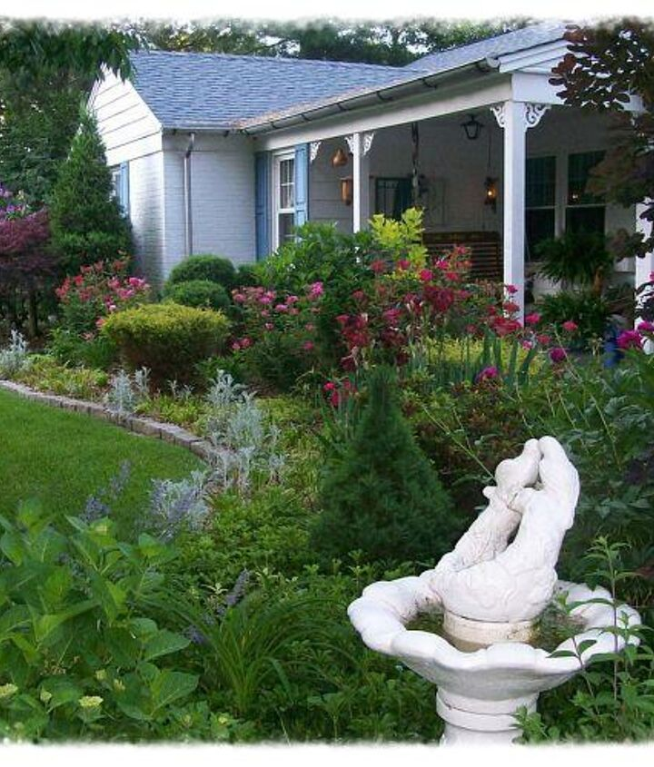 May view of the porch flowerbeds with roses and peonies in their glory.