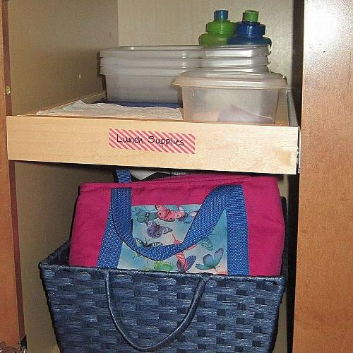 The top pullout shelf holds cups, divided containers, napkins, & notes.  Below, a basket easily pulls out to grab lunch bags.