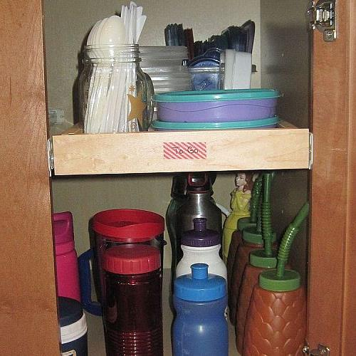 The next cabinet holds smaller plastic containers my husband uses to pack leftovers for work.  The bottom shelf holds all of our water bottles & to-go cups.