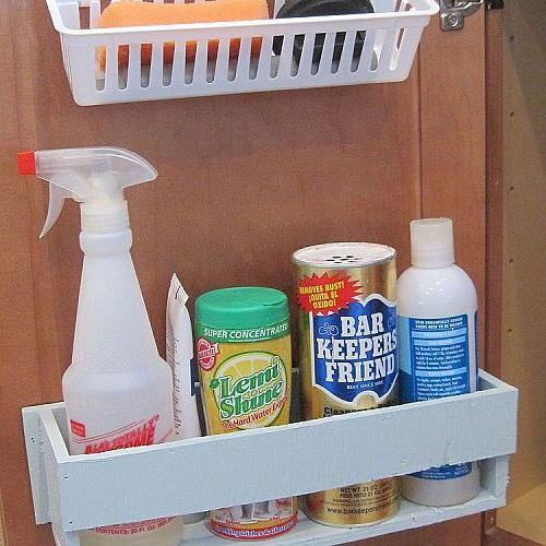 My husband built a cleaning caddy for the door under the sink.  It holds our most-used kitchen cleaners.  Above it, small adhesive hooks hold a plastic container for sponges & scrubbers keeping them in easy reach.