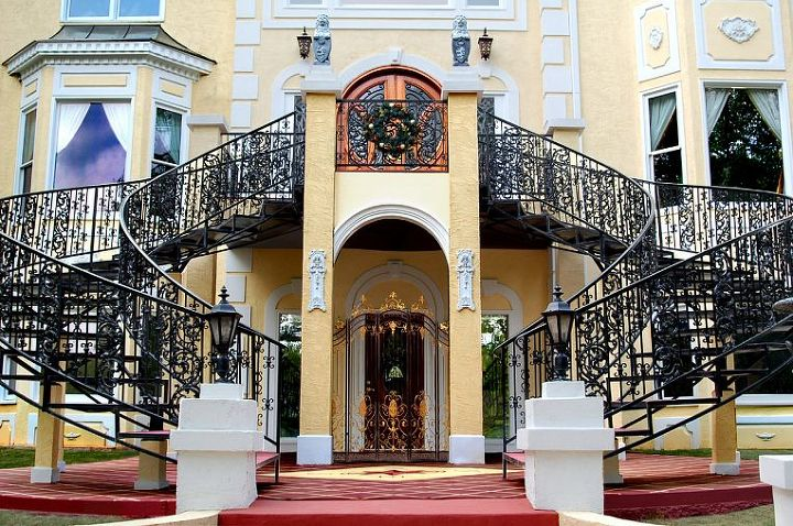 """This image shows the iron double French staircase, as well as both the main entrance (above) and lower """"Guest House"""" entrance (below) as well."""