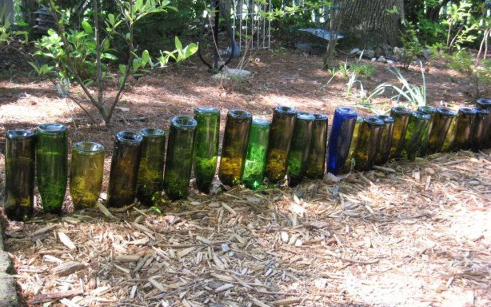 s 15 incredible backyard ideas using empty wine bottles, gardening, outdoor living, repurposing upcycling, Flip bottles and plant them along your garden