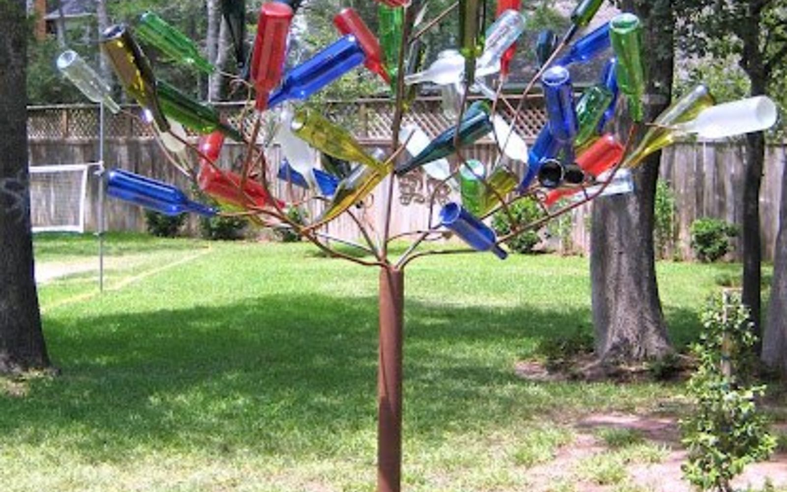 s 15 incredible backyard ideas using empty wine bottles, gardening, outdoor living, repurposing upcycling, Make a bottle tree with stakes in the garden