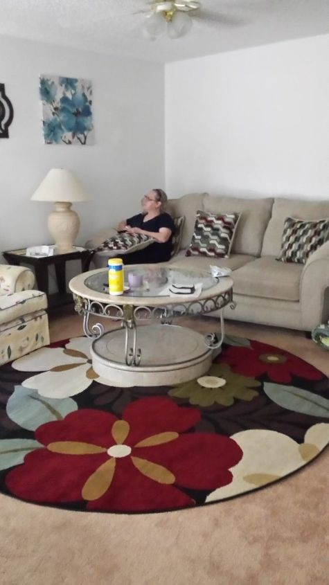 q how to brighten up the living room, home decor, home decor dilemma, just hung up the pics flowing rug taking from by the sliding doors which entrance door is near by noxt to the couch right stairs leads to upstairs
