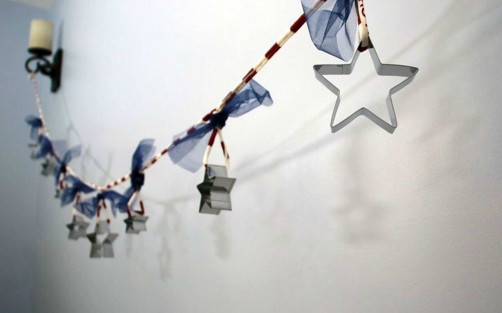 s 13 july 4th decorations that will blow your bbq guests away, crafts, outdoor living, seasonal holiday decor, Hang a garland of Dollar Store cookie cutters