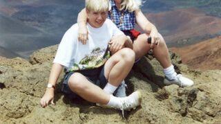 , My son I sitting on white mountains edge into Haleokolea Volcano in Maui Hawaii