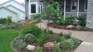 , Considering using this type of an idea for the front brick wall Consider a small growing ornamental tree don t plant too close to house and use perennials