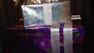 , Wrapped cabinet purple laid on its back set the tree on top to increase its height Then a box silver over the tree base I made two wired ribbon bows tucked them on each side of the tree pole