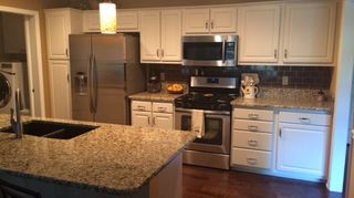 , Totally AFTER picture with cabinets painted subway tile backsplash and neutral color on the walls