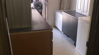 , Old laundry room filled with uninstalled random laminated cabinetry